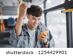 Small photo of Young asian man is standing in the bus using phone and holding onto the bar while waiting to arrive at her destination.