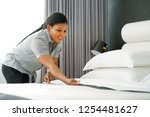 Small photo of Maid making bed in hotel room. Staff Maid Making Bed. African housekeeper making bed.