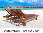 wooden sunbed on tropical... | Shutterstock . vector #1254557434