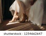 bride wearing wedding shoes.... | Shutterstock . vector #1254662647