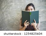 Stock photo closeup woman hand holding a book to read 1254825604
