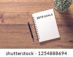 2019 goals list in notebook... | Shutterstock . vector #1254888694