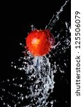 Red apple water splash on black background - stock photo