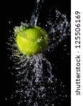 Green apple water splash on black background - stock photo
