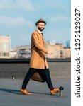 handsome businessman walking on ... | Shutterstock . vector #1255123027
