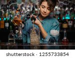 Stock photo female bartender pouring to the measuring glass cup with ice cubes an alcoholic drink from steel 1255733854