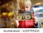 little boy holds a one dollar... | Shutterstock . vector #1255795321