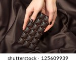 Closeup of female hands holding the dark chocolate bar - stock photo