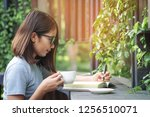 happy young woman writing on... | Shutterstock . vector #1256510071