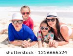 family of four on the beach on... | Shutterstock . vector #1256666524