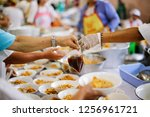 hand offered to donate food... | Shutterstock . vector #1256961721