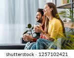 cheerful couple holding cups... | Shutterstock . vector #1257102421