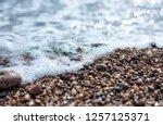 wet stones on the sea shore   Shutterstock . vector #1257125371