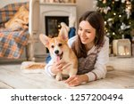 Stock photo little puppy welsh corgi cardigan plays with his leash with a girl in a white sweater 1257200494