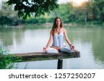 woman doing yoga by the lake.... | Shutterstock . vector #1257250207