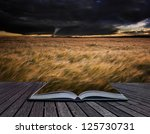 Small photo of Creative concept image of stormy skies over Summer landscape in pages of book