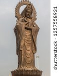 Vertical photo of Guanying Buddha statue at Guiyuan Buddhist Temple in Wuhan Hubei China. Statue towers over courtyard, tower is in background.