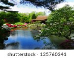 Colorful and picturesque Japanese Tea house with the koi pond in the foreground and the colorful blooming azalea bushes and other flowers around the pond