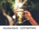 hand holding a mug of beer on... | Shutterstock . vector #1257607444
