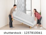 smiling couple carrying modern... | Shutterstock . vector #1257810061