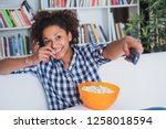 black woman watching tv at home ... | Shutterstock . vector #1258018594
