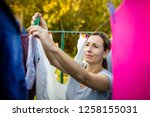 young woman putting laundry on... | Shutterstock . vector #1258155031