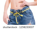 a girl in jeans measures the... | Shutterstock . vector #1258233037