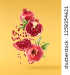 Small photo of Flying in air fresh ripe whole and cut pomegranate with seeds and leaves isolated on yellow background. High resolution image