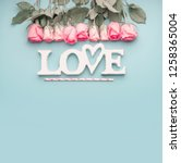Stock photo word love with roses border on pastel blue background top view with copy space valentines day or 1258365004
