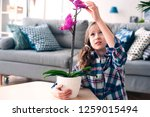 happy kid girl with orchid... | Shutterstock . vector #1259015494