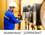 repairman opens gate valve on... | Shutterstock . vector #1259042647