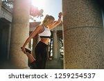woman in fitness wear warming... | Shutterstock . vector #1259254537
