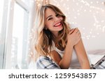 Small photo of Fascinating white girl with light makeup posing in her room. Glad young woman sitting beside window at home and smiling.