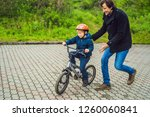 dad teaches son to ride a bike... | Shutterstock . vector #1260060841