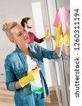beautiful girl cleaning window... | Shutterstock . vector #1260311194