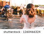 The bride listens to a performance the of favorite band. A wedding with music band. The woman claps and sings along with a song