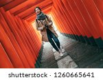 Stock photo full length asian photographer cheerfully walking through red torii gates in tenmangu temple in 1260665641