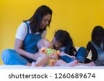 babysitting playing with three... | Shutterstock . vector #1260689674