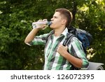 Hiker Drinking Water In Forest