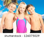 Portrait of the happy children enjoying at beach.  Schoolchild kids standing together in bright color swimwear. - stock photo