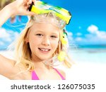 Portrait of the happy girl enjoying at beach.  Schoolchild girl with swimming mask on head. - stock photo