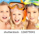 Portrait of the happy children enjoying at beach.  Schoolchild kids standing together in bright color swimwear with swimming mask on head . - stock photo