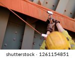Closeup picture of male rope access worker hand wearing safety glove checking inspecting Karabiner which clipping on the tie line prior abseiling working at height construction site, Sydney, Australia - stock photo