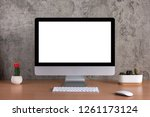 Stock photo blank screen of all in one computer with cactus vases on raw concreate background 1261173124