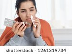ailing woman with pills in hand ... | Shutterstock . vector #1261319734