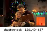 dad reading book for adorable... | Shutterstock . vector #1261404637