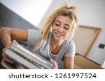 pretty blonde woman packing a ... | Shutterstock . vector #1261997524
