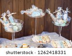 Festive candy bar with a variety of delicious cakes and sweets in blue and orange colors. Candy bar on birthday or wedding celebration.