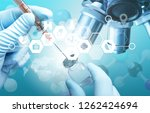hand and laboratory microscope. ... | Shutterstock . vector #1262424694