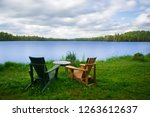 chairs sit on the grass facing... | Shutterstock . vector #1263612637